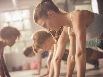 Junge Frauen in Stützposition bei Workout in einem Fitnesskurs | © Getty Images