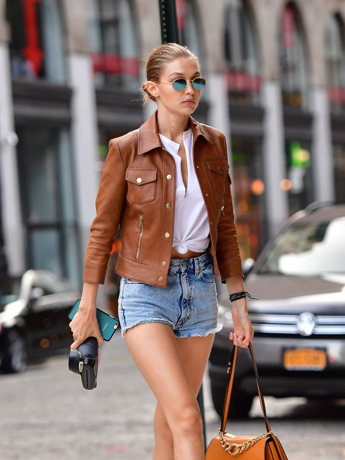Model Gigi Hadid mit Sonnenbrille, brauner Bikerjacke, Jeansshorts und Handtasche in New York City | © Getty Images | James Devaney