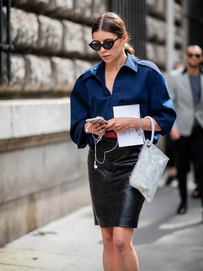 Besucherin der Paris Fashion Week mit Sonnenbrille, blauer Oversize-Bluse, Handtasche und Pencil Skirt aus Leder | © Getty Images | Christian Vierig
