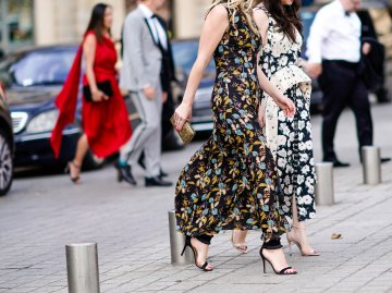 Street Style von zwei Besucherinnen der Paris Fashion Week 2018 in langen Kleidern mit Blütenprint und High Heels | © Getty Images / Edward Berthelot