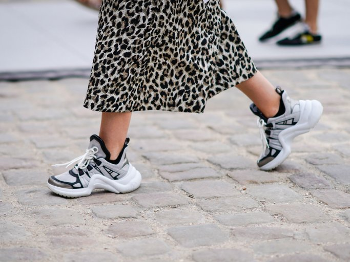 "Detailaufnahme des Streetstyles einer Besucherin der Pariser Fashion Week in ""Dad Sneakers"" von Louis Vuitton zum Midirock mit Animal Print 
