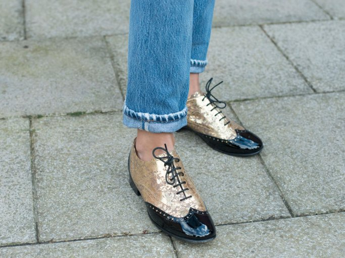 Detailaufnahme des Streetstyles der Influencerin Soraya Bakhtiar in gold-schwarzen Brogues von Chanel und Straight Leg-Jeans bei der Fashion Week in London | © Getty Images / Kirstin Sinclair