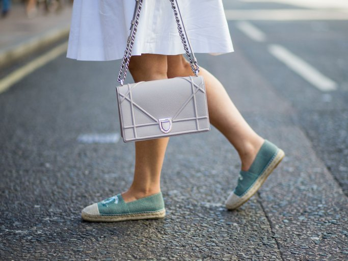 Streetstyle einer Besucherin in weißem Kleid, türkisfarbenen Chanel-Espadrilles und mit Dior Handtasche bei der Menswear Fashion Week in London | © Getty Images / Christian Vierig