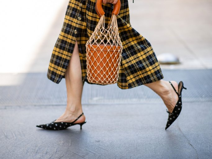 Detailaufnahme einer Besucherin in kariertem Rock und Kitten Heels mit Beuteltasche auf der Menswear Fashion Week in Mailand | © Getty Images / Christian Vierig