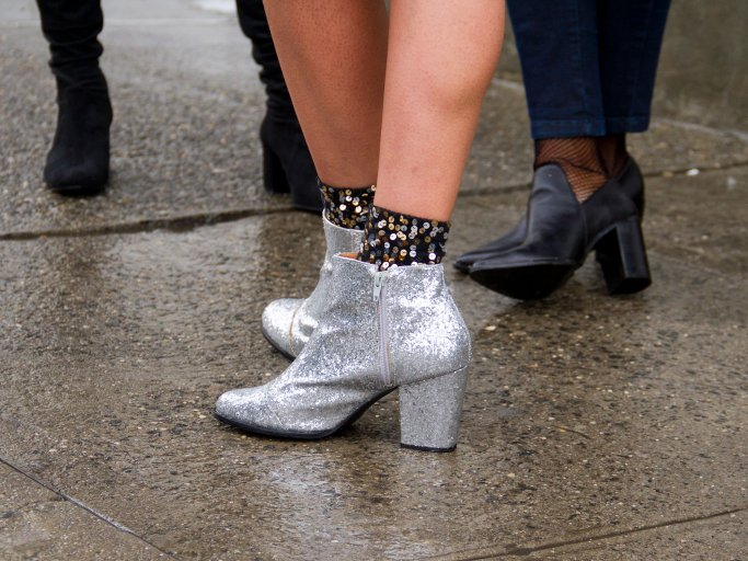 Detailaufnahme des Streetstyles einer Besucherin in silberglitzernden Ankle Boots und Paillettensöckchen bei der Fashion Week in London | © Getty Images / Georgie Hunter