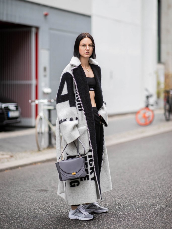 Maria Barteczko wearing wool coat Celine, black cropped top 032c, black leggings Balenciaga, sneakers Nike, necklace Suenos letter, grey bag Wandler | © Getty Images | Christian Vierig