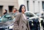 Tiffany Hsu wears a checked coat, a checked blazer jacket, a white top, black boots | © Getty Images | Edward Berthelot